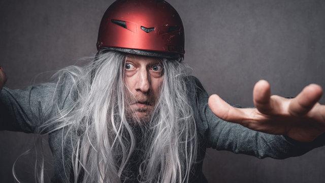 Portrait skuril crazy Mann graue lange Haare mit rotem Helm