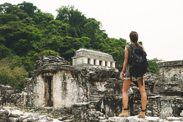 Woman with a backpack beside ancient Mayan ruins Fototapete