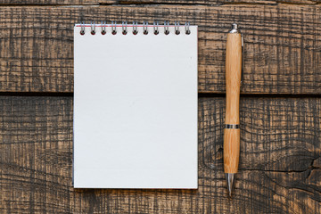 Empty white notebook and pen on the wooden table. Top view, high resolution picture. Empty space in the notebook ready to insert graphics or text.