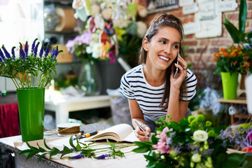 Obraz Cheerful florist on phone with client and writing down their order - fototapety do salonu