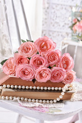 vintage style picture with bunch of pink roses lying on books