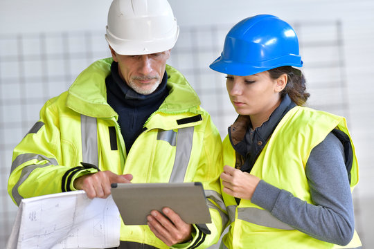 Instructor with apprentice on construction site working with tablet