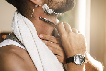 Man shaving his beard with a straight razor