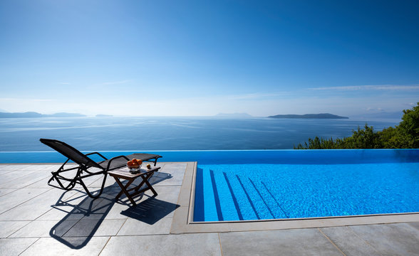 Infinity pool with chairs  With a view of the sea