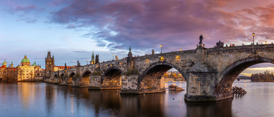 Prague, Czech Republic - Panoramic view of the world famous Charles Bridge (Karluv most) and St. Francis Of Assisi Church on a winter afternoon with beautiful purple sunset and sky