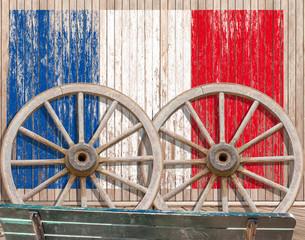 drapeau français sur fond bois, roues de charrette et banc