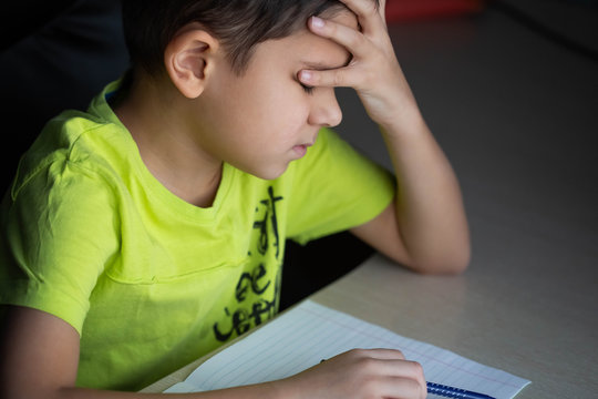 The child,  the schoolboy does not want to do difficult homework, sits at the table, bored