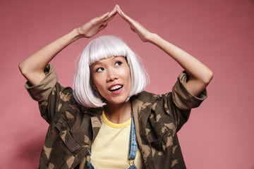 Image of asian girl in white wig making roof above her head with arms