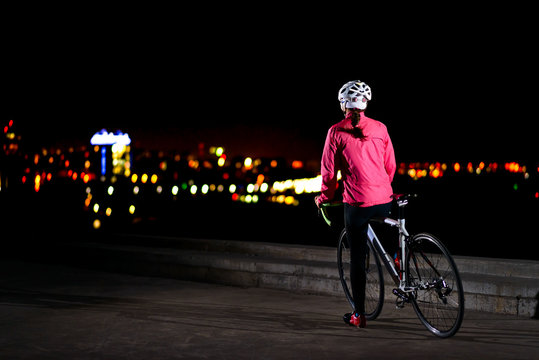 Woman Cyclist Resting with Road Bike and Looking at Night City Lights. Healthy Lifestyle and Urban Sport Concept