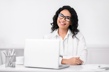 Smiling latin businesswoman working at modern office