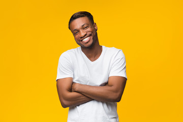 African American Man Smiling Crossing Hands Standing Over Yellow Background