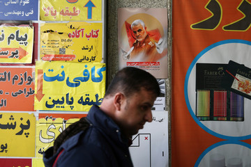 A man walks past a picture of Iranian Major-General Qassem Soleimani, head of the elite Quds Force, who was killed in an air strike at Baghdad airport, in Tehran