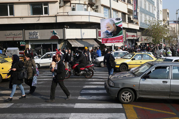 Iranian people walk past a picture of Iranian Major-General Qassem Soleimani, head of the elite Quds Force, who was killed in an air strike at Baghdad airport, in Tehran