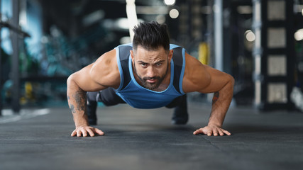 Wall Mural - Strong guy making plank or push ups exercise