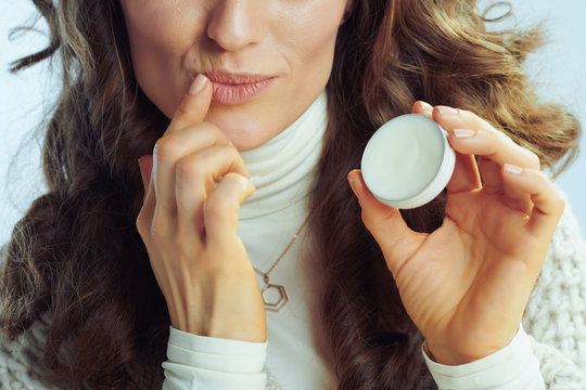 Closeup on modern housewife applying lip balm