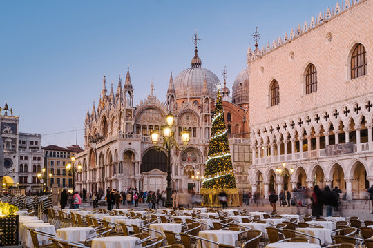 Venice, Italy, 23 December 2019 - People walking in San Marco square in the evening. On the square the Christmas tree with lights and decorations in front of the Doge's Palace