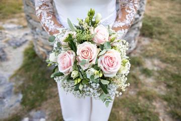 Détail de la robe de la marié avec son bouquet le jour de son mariage