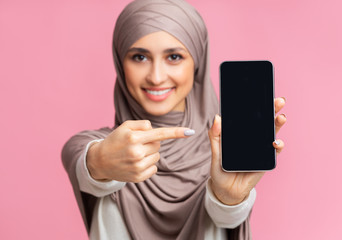 Muslim girl holding smartphone with black screen and pointing at it