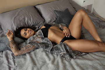 Portrait of a sensual sexy african woman lying on the bed in black lingerie