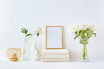 Home interior with decor elements. Gold frame, white peonies in a vase, interior decoration