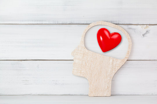 Human Head and Red Heart inside brain shape over white wood background. Symbol for falling or being in love, liking, emotions and affection Concept with copy space.