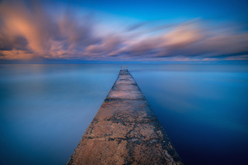 Long exposure seascape fine art photograph of pier on a sunrise in Paphos, Cyprus