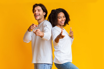 Positive interracial couple pointing at camera with index fingers, picking somebody