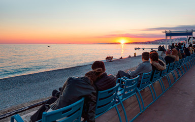 Wall Mural - People sitting and watching sunset near the Mediterranean sea- Nice, France