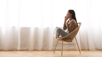 Happy girl talking on phone, sitting in modern armchair