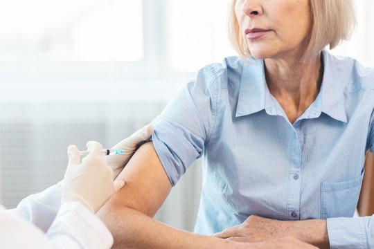 Closeup nurse doing vaccination to senior woman