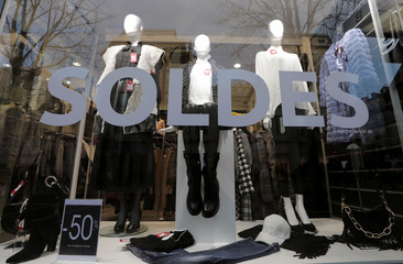 A discount sale sign is seen on a shop window on the eve of the start of winter sales in Nice