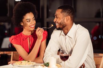 Loving Afro Couple Having Date Feeding Each Other In Restaurant
