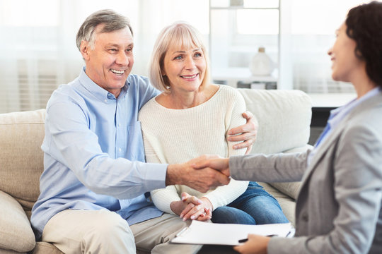 Female realtor handshaking happy mature couple at home