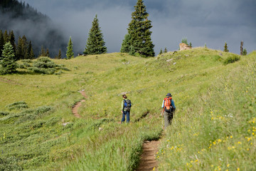 Two backpackers hiking along the trail to Twilight Peak in the Weminuche Wilderness near Silverton, Colorado