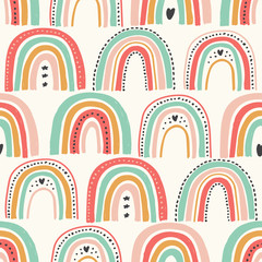 Cute scandinavian childish seamless pattern with trendy hand drawn rainbows