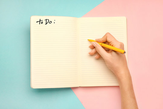 Woman making to-do list on color background