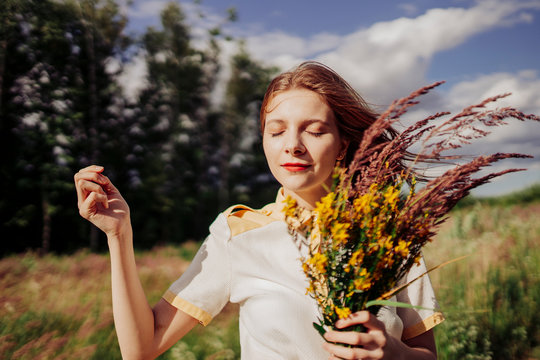 Woman with eyes closed standing with flowers in field