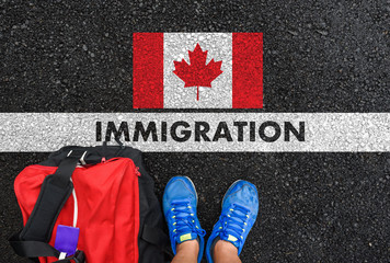 Man in shoes with bag standing next to line with word IMMIGRATION and flag of Canada on asphalt road