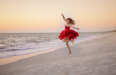 Young girl dancing and twirling on beach in a red dress