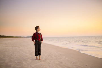 Young boy standing on the beach at sunset