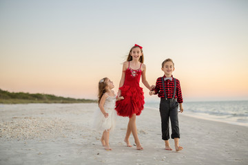 Siblings walking and smiling on the beach at Christmas