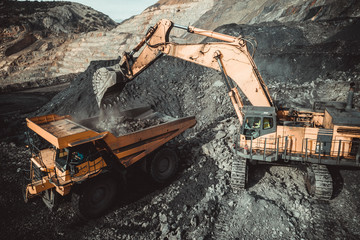 High angle view of excavator loading coal in dumper truck