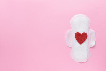 Menstrual pad with red heart on color background. Menstruation concept