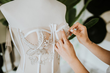 close up of hands sewing a wedding dress