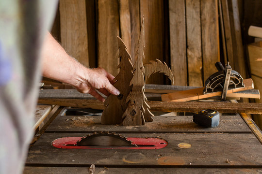Close-up of a man cutting wooden trees with circular saw on workbench