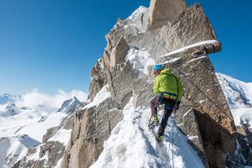 Rear view of man climbing rocky mountain in winter