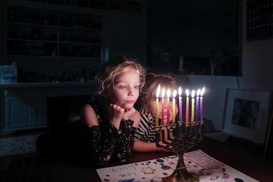 Siblings looking at Hanukkah illuminated on table