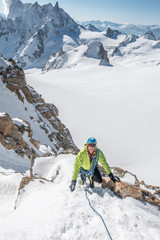 Alpinist smiles as he follows up steep snow high above the glacier