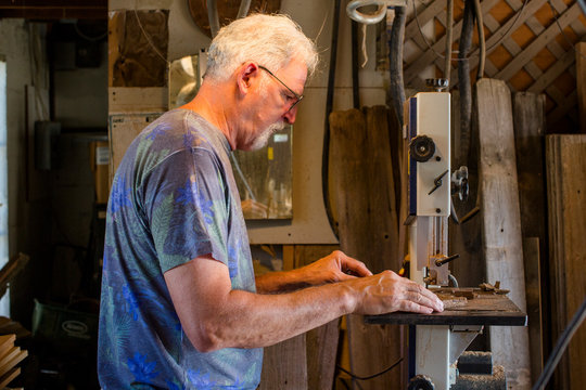 Side view of an elderly gentleman cutting wood with a band saw