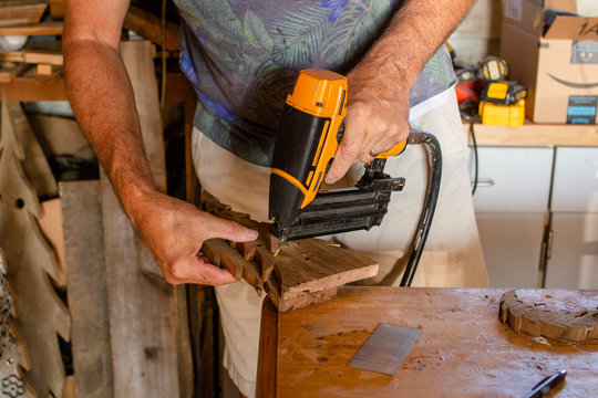 Above view of a men using a hand drill in his woodworking shop